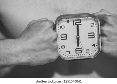 Alarm clock show six oclock between male fists. Power, strength, health. Morning, wake up concept