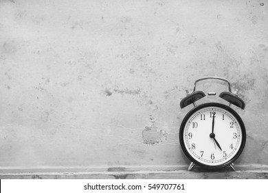 alarm clock showing five o'clock on wooden background, black and white image