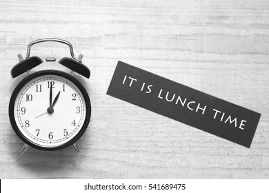 alarm clock showing one o'clock and indicating to have lunch. black and white