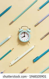 Alarm clock shows 8 oclock in morning, time to go to school concept. Creative Flat lay with clock and geometric pattern from blue pens and pencils on beige background.