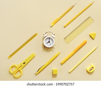 Alarm clock shows 8 oclock in morning, time to go to school concept. Creative Flat lay with clock and stationary school supplies in yellow pastel colored.