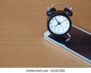 alarm clock and smartphone on brown background