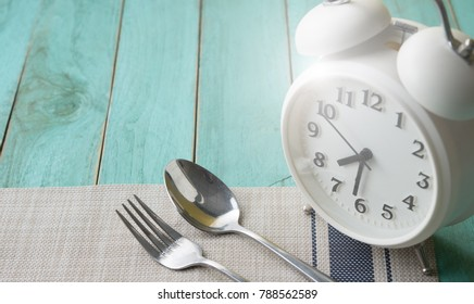 Alarm clock with spoon and fork on wooden background,Time eating concept