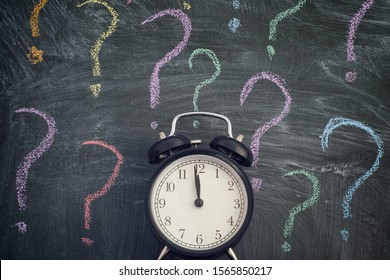 Alarm clock standing against blackboard with colorful question marks. Few minutes before deadline. Close up.