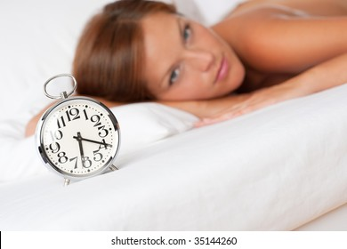 Alarm clock standing on bed, woman in background, shallow DOF