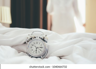 Alarm clock standing on bedside table has already rung early morning to wake up woman is stretching in bed in background.Relaxing concept.