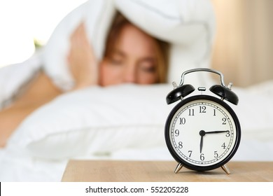 Alarm clock standing on bedside table going to ring while woman cover head and ears with pillow making unpleasant face. Early awakening, not getting enough sleep, oversleep, getting work time concept