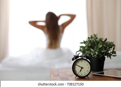 Alarm clock standing on bedside table has already rung early morning to wake up woman is stretching in bed in background. Early awakening, not getting enough sleep, oversleep concept