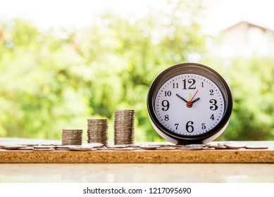 alarm clock and step of coins stacks, nature background, money, saving and investment or family planning concept, over sun flare silhouette tone.