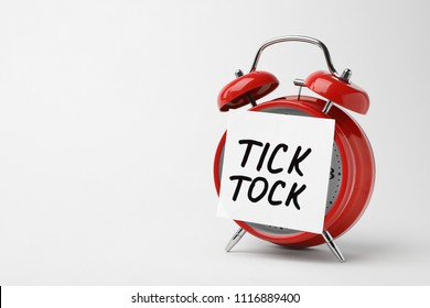 Alarm clock and sticky note with words TICK TOCK on white background. Time concept