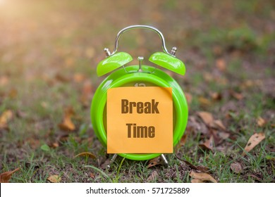 Alarm clock with sticky paper written BREAK TIME over  blur background