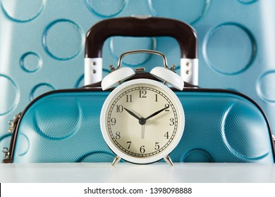 Alarm clock and suitcases close-up. Departure in time concept. Boarding time.
