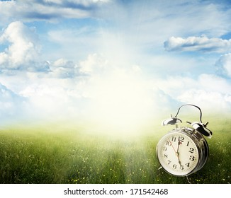 Alarm clock in sunlit spring field