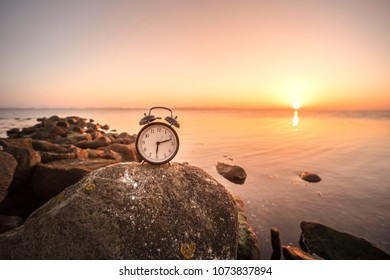 Alarm clock in the sunrise by the sea on a large rock by the shore