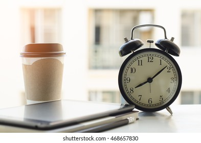 Alarm clock, tablet computer, paper note book and coffee cup on wooden desk by the window in morning light. Overtime working concept. Part time job, home office, working at home.