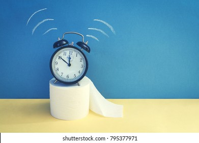 Alarm clock with toilet paper on a yellow background. Natural remedy for constipation