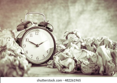 Alarm clock in a wastepaper concept for a time waste of time with golden bokeh blur texture background