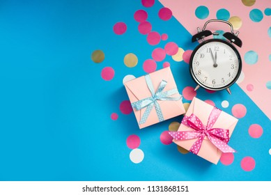 The alarm clock, which shows almost midnight among the multicolored confetti and present boxes, as the concept of celebrating the New Year.