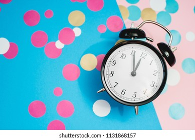 The alarm clock, which shows almost midnight among the multicolored confetti, as the concept of celebrating the New Year.