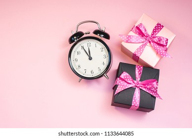 The alarm clock, which shows almost midnight and a present boxes, as the concept of celebrating the New Year.