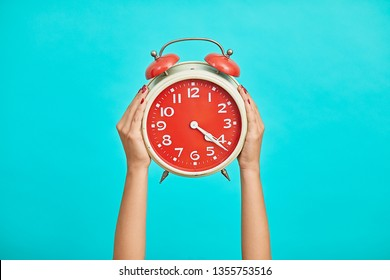 Alarm clock in woman hands, Woman hand holding the red vintage alarm clock on bright blue background.