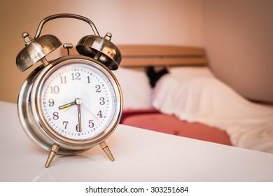 alarm clock with woman sleeping in bedroom