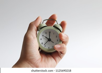 An alarm clock and a woman's hand.
