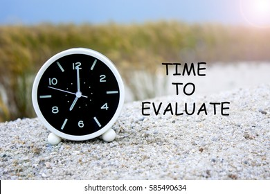 alarm clock with word time to evaluate concepts isolated on grass tree background