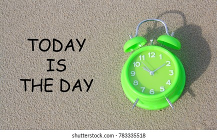 Alarm clock with word today is the day isolated on sand background