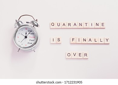 Alarm clock and words end of quarantine on pastel background. Creative flat lay, quarantine is over or back to normal life concept. When coronavirus lockdown ends theme