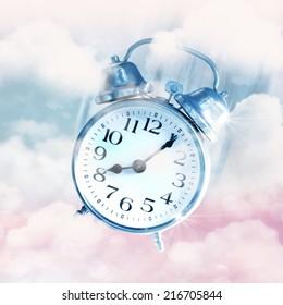 Alarm clocks flying on blue sky, time flies concept.