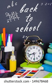 alarm clocks and school supplies on the background