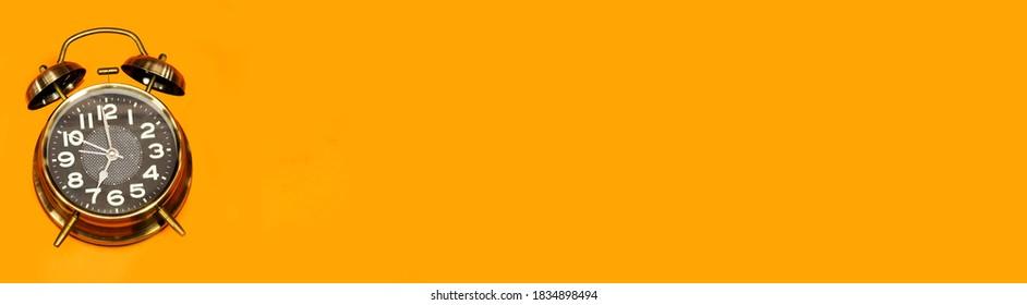 alarm o'clock showing 7 o'clock isolated on orange background