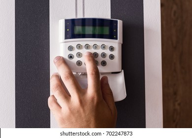 Alarm panel. Protection of the apartment and the house. The house is protected. A man's hand puts a siglanizuyu on the remote control