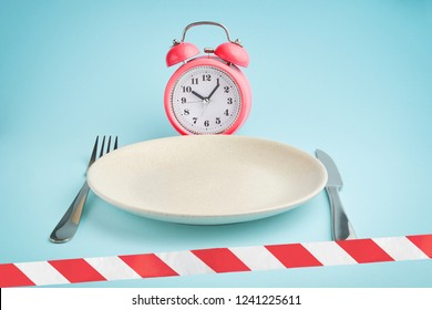 Alarm clock? plate with cutlery and barrier tape. Concept of intermittent fasting, lunchtime, diet and weight loss