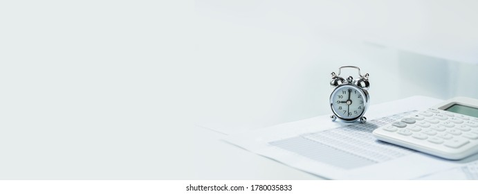 Alarmclock with calculator on financial paperwork. Finance and business concept blue banner. Deadline and application or reporting window.