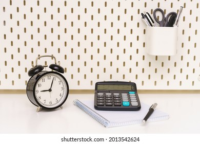 alarmclock, calculator, pen and a notebook placed on white background