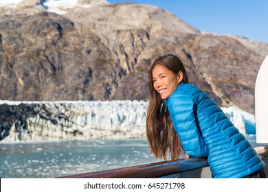 Alaska cruise ship tourist looking at glacier front in Glacier Bay National Park, USA. Woman on travel vacation sailing enjoying view of Margerie Glacier.