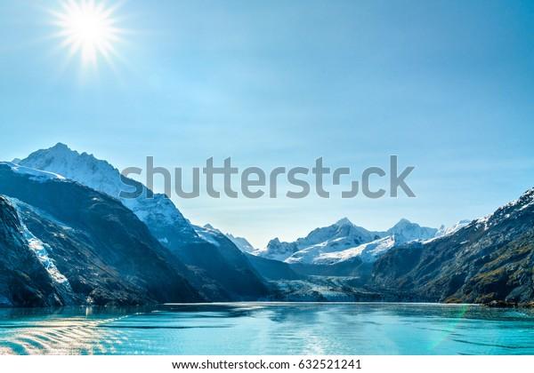 Alaska cruise travel landscape. Glacier Bay Johns Hopkins Glacier on sunny day with sun flare. Summer vacation in Alaska, USA.