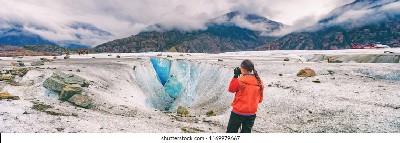 Alaska cruise travel tourist taking photo on activity excursion glacier hike in nature. Banner panorama of woman photographer on summer vacation in USA.