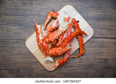 Alaskan King Crab Legs cooked seafood on wooden cutting board background / red crab hokkaido