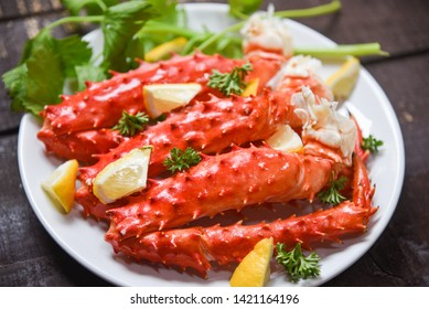 Alaskan King Crab Legs cooked seafood with lemon spices on white plate in the wooden table / red crab hokkaido