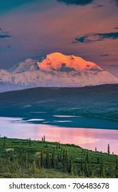 alaska's mount denali looms behind wonder lake at colorful sunset with alpenglow