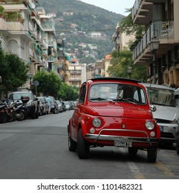 ALASSIO, ITALY - JULY 25, 2006: Old italian car FIAT 500 pictured on the old italian street. Red color vintage car still on the road.