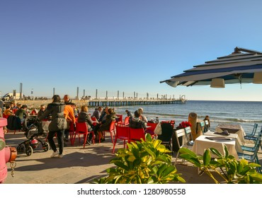 Alassio, Liguria / Italy - 01 02 2019: Tourists sitting in a outdoor café on the walkway of the beach with the pier in the background