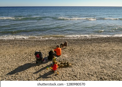 Alassio, Liguria / Italy - 01 02 2019: Family with dog on the sandy beach in a sunny winter day
