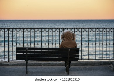 Alassio, Liguria / Italy - 01 02 2019: Woman with hooded parka sitting on a bench in front of the sea at sunset in winter