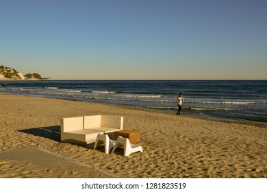 Alassio, Liguria / Italy - 01 02 2019: Scenic view of the sandy beach with a woman jogging on the shore and the Gallinara Island on the background at sunset