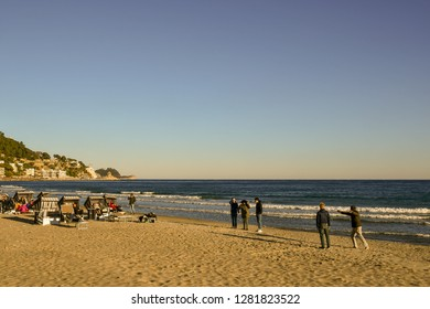 Alassio, Liguria / Italy - 01 02 2019: Tourists playing boules and sunbathing on the sandy beach in a sunny winter day