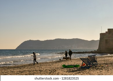 Alassio, Liguria / Italy - 01 02 2019: Scenic view of the sandy beach with a woman jogging on the shore, a couple with their dogs, the Saracen Tower (Torrione Saraceno) and Capo Mele cape